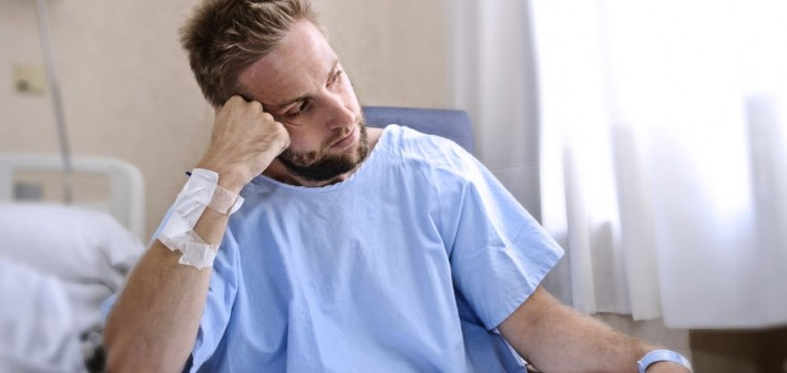 42892280 - young injured man in hospital room sitting alone in pain looking negative and worried for his bad health condition sitting on chair suffering depression on a sad lonely medical background