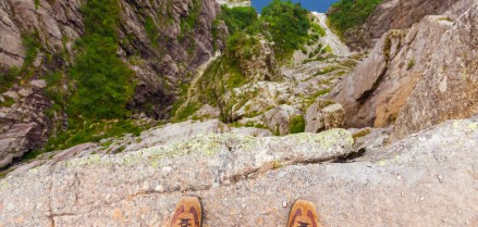 36965232 - man standing on cliff preikestolen in fjord lysefjord - norway - nature and travel background